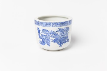Ancient tea cup with the dragon painted with the blue ink on white background