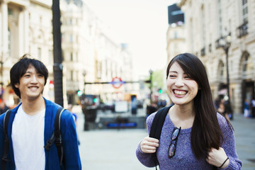Young Japanese man and woman enjoying a day out in London, walking near Piccadilly Circus.