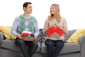 Man and woman knitting together on a sofa