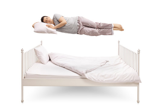 Young man sleeping and floating above a bed