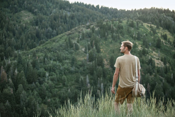A man in the mountains standing looking around him.