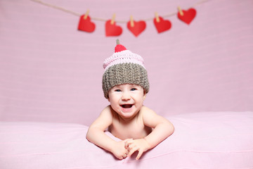 cute joyful baby with a knitted hat on a pink background