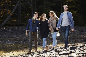 Four people walking along, couples hand in hand, on the shore of a lake.