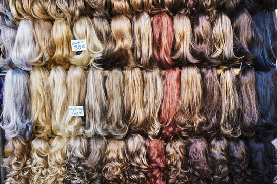 A display of hair extensions and hair pieces of different colours.
