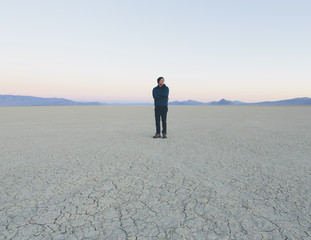 Man standing on cracked desert