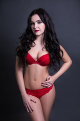 sexy beautiful plus size model in red lingerie over black backgr