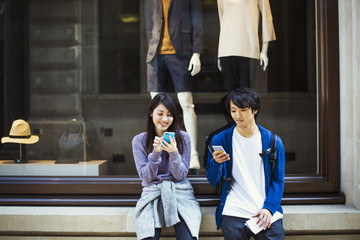 Young Japanese man and woman enjoying a day out in London, using a smartphone.