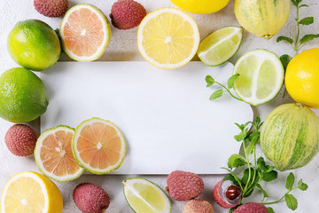 Variety of whole and sliced citrus fruits pink tiger lemon, lemon, lime, mint and exotic lichee with empty cutting board over white concrete background. Top view, space for text, healthy eating