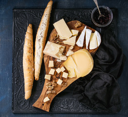 Cheese plate. Assortment of cheese with walnuts, jam and bread on olive wood serving board with textile over black ornate and dark blue canvas as background. Top view with space.