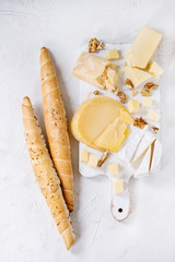 Cheese plate. Assortment of cheese with walnuts and bread on white wood serving board over white concrete texture background. Top view with space.