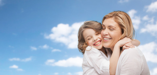 happy mother and daughter hugging over blue sky