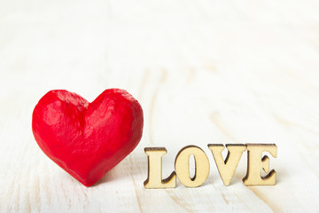 Red heart and the word love made of wooden letters on a white background
