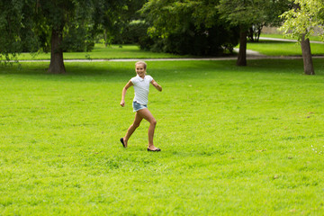 happy girl running and playing at summer outdoors