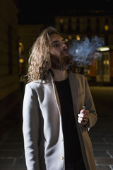 Stylish young man smoking outdoors at night