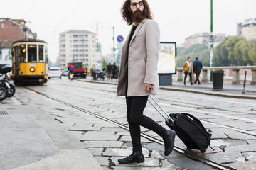 Stylish young man with suitcase crossing tramway