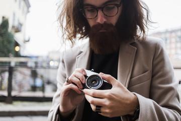 Stylish young man outdoors holding camera