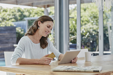 Woman sitting on terrace, doing online payment with credit card