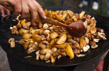 Roasted potatoes with meat cooked in metal cauldron pot