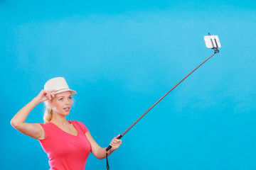 Woman taking picture of herself with phone on stick
