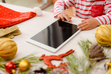 Happy Christmas background. Top view on child hands using tablet computer with toys and Santa Claus hat on light wooden table.