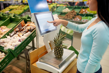 woman weighing pineapple on scale at grocery store