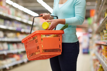 woman with food basket and jar at grocery store