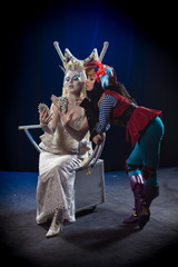 The plot of the play. Two actresses woman in makeup and costume of the Snow Queen and pirate photographed in the studio on blue-black background