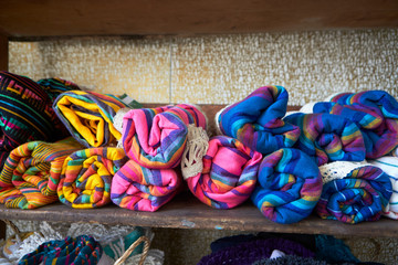 Colourful blankets on shelves in store, close up, front view