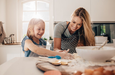 Happy young girl with her mother making dough