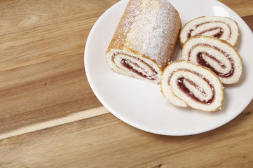 A strawberry jam Swiss roll cake on a wooden counter top background with blank space at side