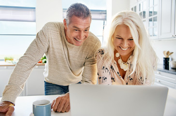 Laughing middle aged couple looking at computer