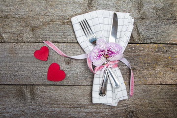 Fork, knife, orchid on white checkered napkin with red ribbon