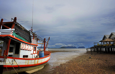 landscape with stranded boat and vacation resort on low tide beach in Koh Lanta island province of Krabi