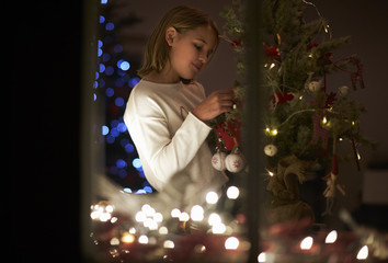 Evening Shot Of Girl At Home Decorating Christmas Tree