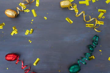 Carnaval golden confetti and curling paper decorations on dark wooden background