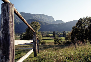 Fototapete - Alpine valley and rustic fence