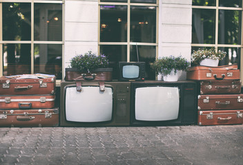 Lots vintage tv set with old retro suitcases and house plants in