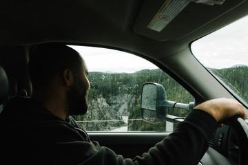 Man looking at landscape through car window