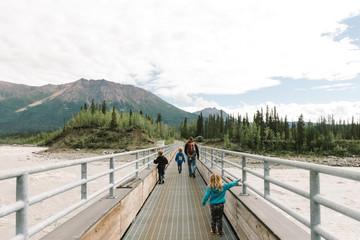 Family walking on footbridge towards woodland landscape