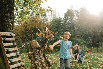 Siblings throwing autumn leaves in garden