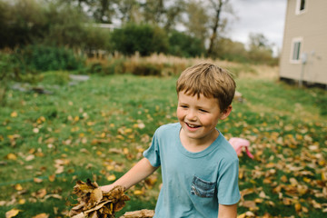 Young boy holding autumn leaves