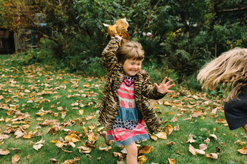 Children throwing autumn leaves