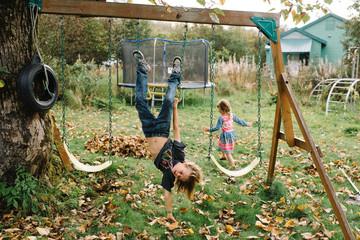 Siblings playing on swings in garden