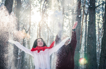 Couple throwing snow in winter forest