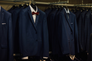 Classic suits in boutique. Luxury mens classic suits on rack in elegant men's boutique. Shopping concept