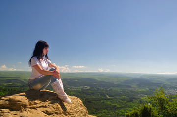 A girl sits on the edge of a cliff and looking into the distance