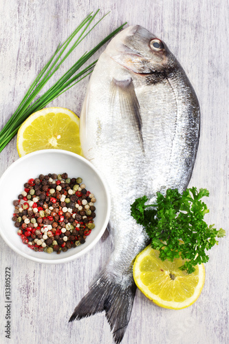 Photo: Fresh uncooked sea bream fish with lemon, aromatic herbs and ...