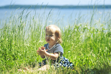 Girl sitting in the grass on the bank of the river