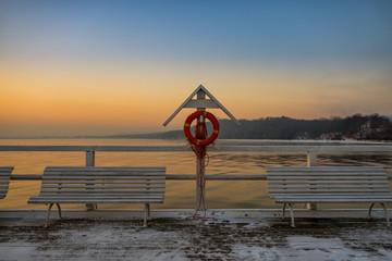 Zimowy wschód słońca na molo, koło ratownicze