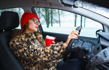 Beautiful woman in a fur coat and red hat with coffee to go driv
